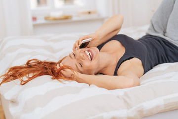 Vivacious woman relaxing in bed laughing