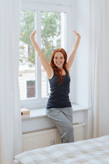 Cheerful woman standing by window in bedroom