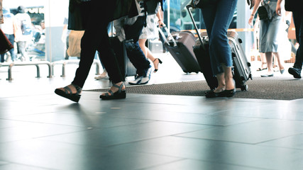 Unrecognizable people with baggages walking in terminal airport. Close up of them legs