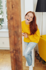 Laughing playful young woman indoors at home