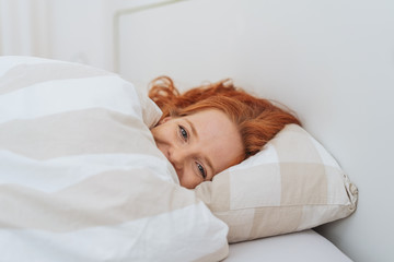 Laughing young woman cuddling under the duvet