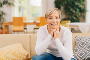 Attractive mature blond woman relaxing on a sofa