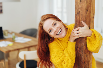 Happy young woman hanging onto a wooden post