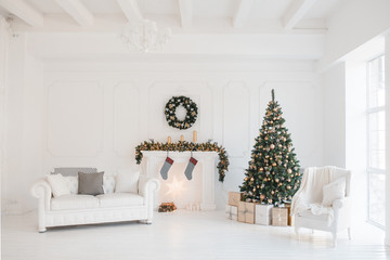 Christmas and New Year decorated white interior room with presents and New year tree and fireplace