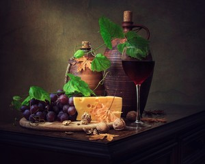 Still life with grapes, red wine and cheese
