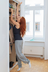 Young woman stretching to reach her clothes