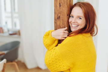 Young smiling woman hugging a wooden pole