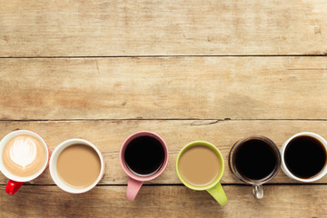 Many multicolored cups with coffee and coffee drinks lined up on a wooden background. Concept breakfast with coffee, coffee with friends. Flat lay, top view