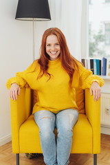 Trendy young redhead woman sitting in an armchair