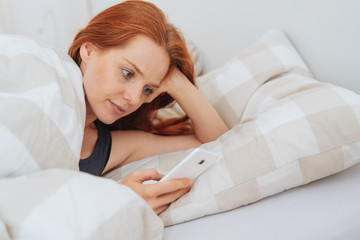 attractive redhead woman using a mobile in bed