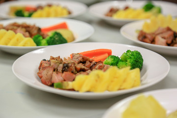Steak pork sliced cube with vegetables such as tomatoes, carrot, broccoli and pineapple.