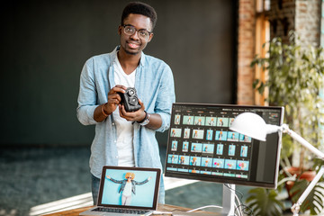 Portrait of a young african ethnicity photographer standing with retro camera near the working place with computers in the studio