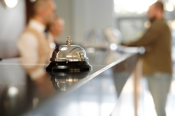 Modern luxury Hotel Reception Counter desk with Bell. Service Bell locating at reception. Silver Call Bell on table, Receptionists and customer on background. Сheck in hotel. Concept. Wall mural