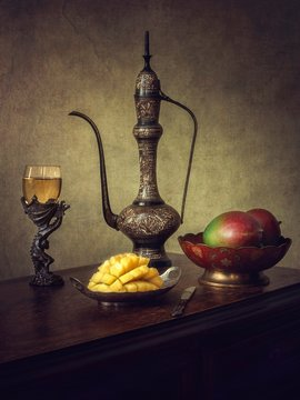Still life with mango and white wine
