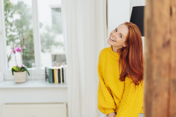 Relaxed happy young redhead woman indoors