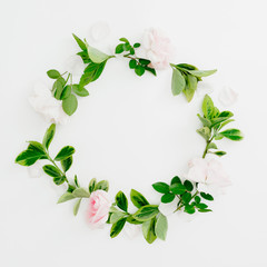 Floral round frame of pastel pink roses and green leaves on white background. Flat lay, top view. Spring time composition