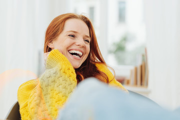 Young woman sitting indoors laughing