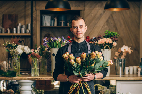 Man florist holding a protea flowers arrangements in modern interior floral shop. Small business, welcoming concept.