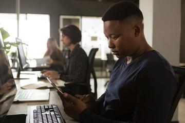 Executive using digital tablet at desk