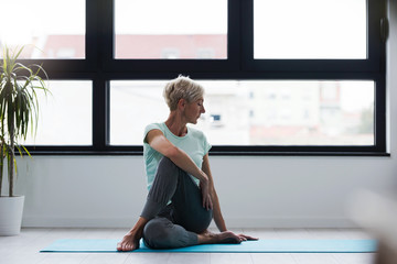 Active senior woman practicing yoga indoors. Exercise for Older Adults