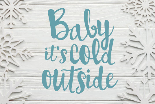 """flat lay with decorative snowflakes on white wooden background with """"Baby its cold outside"""" lettering"""