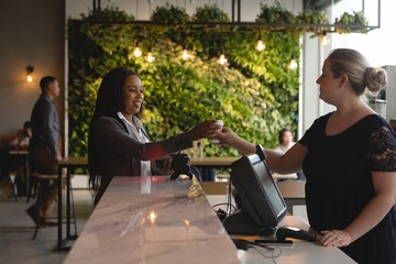 Waitress serving coffee to female executive at counter