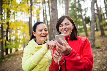 Two female runners outdoors in forest in autumn nature, using smartphone.