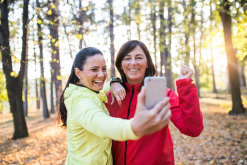 Two female runners with smartphone taking selfie outdoors in forest in autumn nature.