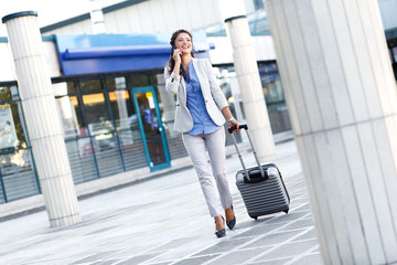 Young woman on business trip walking with her luggage and talking at phone at airport.