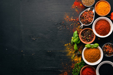 Wall Mural - Spices and herbs on a wooden board. Pepper, salt, paprika, basil, turmeric. On a black wooden chalkboard. Top view. Free copy space.