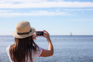 Young travelling woman in hat taking photos of summer sunny sea with smartphone camera.