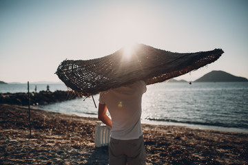 Young man on the beach under an umbrella in the form of a large Vietnamese hat
