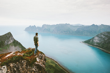 Active man traveling walking alone on cliff mountain edge above sea adventure healthy lifestyle summer vacations outdoor in Norway solitude emotions