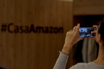 A woman takes a picture with her phone during the presentation of Amazon's first pop-up store in Spain, in an old building in one of prime shopping districts in Madrid