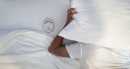 Young man Sleep in the bedroom on the white have a white alarm clock is located nearby, Concept wake up to the morning by the alarm clock.