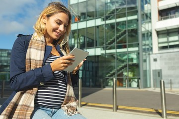 Pregnant woman using digital tablet in the city