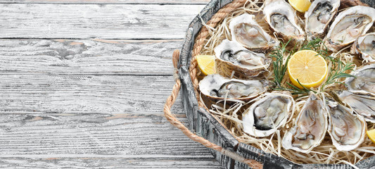 Fresh oysters with lemon in Wooden Box. On a white wooden background. Top view. Free copy space.