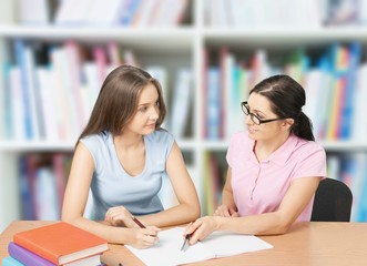 Mother helping happy daughter with homework on background