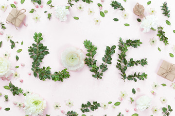 Top view of word Love made of flowers and leaves on white pink b