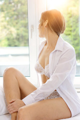 Young attractive woman in lingerie as underwear sits relaxed on bed and looks out of the window
