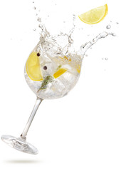 lemon slice falling into a splashing gin tonic