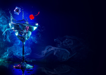 ice and cherry falling in a cocktail splash on blue smoky background