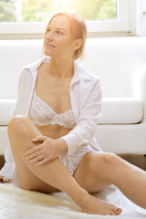 Young attractive woman in lingerie as underwear sits relaxed at home in front of the couch