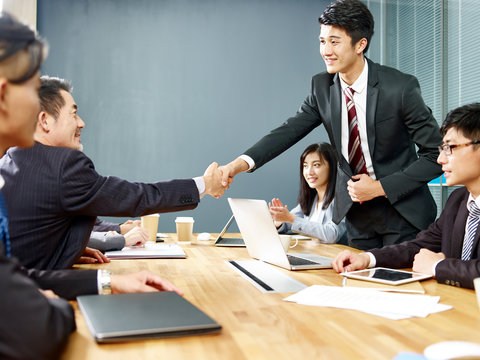 asian corporate executives shaking hands