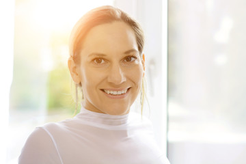 Young attractive woman in portrait nicely smiles on a sunny day