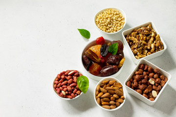 Foto op Aluminium Buffet, Bar Various Nuts in a ceramic bowl and Dried Fruits on a light stone table. The Concept of a Healthy Dessert. Copy space.