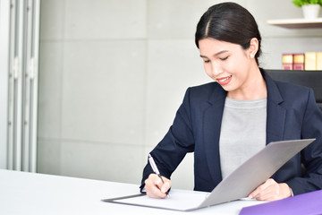 Happy businesswoman signing a contract or document in a desk at office