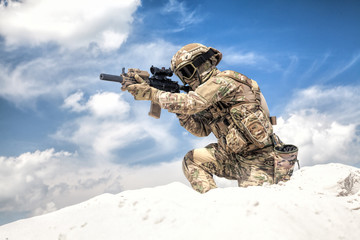 Man in military camouflage uniform with service rifle replica, standing on top of sand dune with cloudy sky on background, imitating U.S. army special forces shooter during airsoft war games in desert