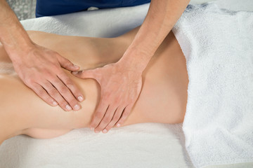 View from above of hands of masseur massaging back of client