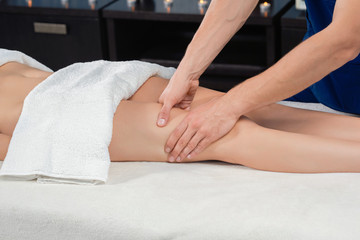 Hands of masseur massaging quadriceps of female in spa salon